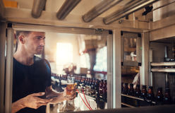 Young man examining beer at brewery. Young man with a glass of beer at brewery plant. Male inspector working on alcohol manufacturing factory checking the beer Royalty Free Stock Image