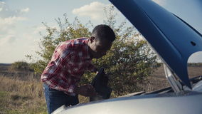 Young man examining car engine. stock video footage
