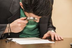 Young Man Examining Contract with Magnifying Glass Royalty Free Stock Photography