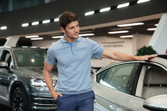Young man examining and looking carefully at his new car. At a dealership royalty free stock photography
