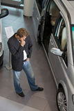 Young man examining new car at showroom Stock Photography