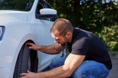 Man examining tires at his new car royalty free stock image