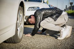 Young Man Examining Underside of Car Stock Photo