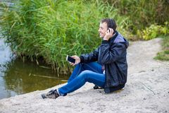 A young man sits on the river bank with a phone and listens to music with headphones Stock Photography