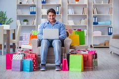 The young man after excessive shopping at home. Young man after excessive shopping at home Royalty Free Stock Photos