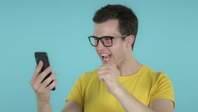 Young Man Excited for Success while Using Smartphone Isolated on Blue Background. The Young Man Excited for Success while Using Smartphone Isolated on Blue stock footage