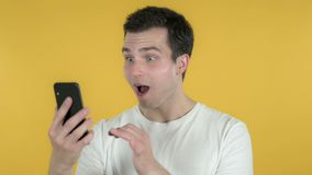 Young Man Excited for Success while Using Smartphone Isolated on Yellow Background. The Young Man Excited for Success while Using Smartphone Isolated on Yellow stock video
