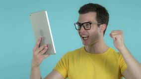 Young Man Excited for Success while Using Tablet Isolated on Blue Background. The Young Man Excited for Success while Using Tablet Isolated on Blue Background stock video