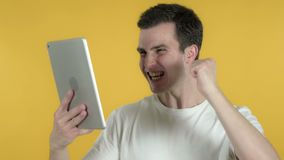 Young Man Excited for Success while Using Tablet Isolated on Yellow Background. The Young Man Excited for Success while Using Tablet Isolated on Yellow stock video