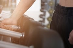 Young man execute exercise in fitness center. male athlete choos. E dumbbell in gym. sporty asian guy working out in health club Royalty Free Stock Photos