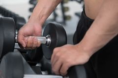 Young man execute exercise in fitness center. male athlete choos. E dumbbell in gym. sporty asian guy working out in health club Royalty Free Stock Photo