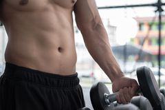 Young man execute exercise in fitness center. male athlete choos Stock Photo