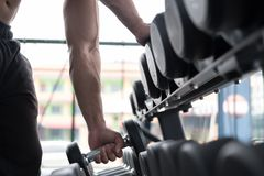 young man execute exercise in fitness center. male athlete choose dumbbell in gym. sporty guy working out in health club. royalty free stock photos