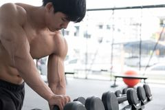 Young man execute exercise in fitness center. male athlete choos. Young man use mobile phone in fitness center. male athlete listen to music in cellphone in gym Royalty Free Stock Image