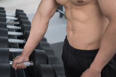 Young man execute exercise in fitness center. male athlete choos Stock Photography