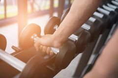 Young man execute exercise in fitness center. male athlete choos Royalty Free Stock Photography