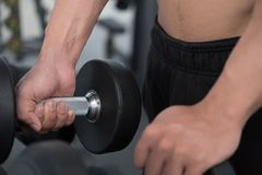 Young man execute exercise in fitness center. male athlete choos Royalty Free Stock Photos