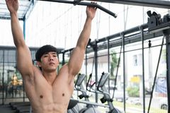 young man execute exercise with machine in fitness center. male athlete training in gym. sporty guy working out in health club. stock images