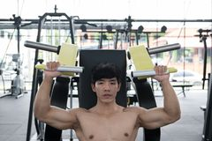 Young man execute exercise with weightlifting machine in fitness Stock Images