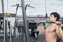Young man execute exercise with weightlifting machine in fitness Stock Photo