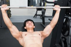 Young man execute exercise with weightlifting machine in fitness Royalty Free Stock Photo