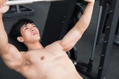 Young man execute exercise with weightlifting machine in fitness Royalty Free Stock Photography