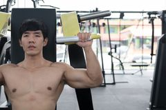 Young man execute exercise with weightlifting machine in fitness Stock Photography