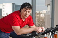 Young man on exercise bicycle Stock Photo
