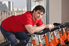 Young man on exercise bicycle Stock Image