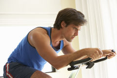Young Man On Exercise Bike Stock Photography