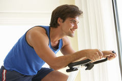 Young Man On Exercise Bike Royalty Free Stock Images