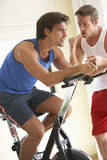 Young Man On Exercise Bike With Trainer Royalty Free Stock Photos