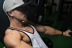 Young Man Exercise Chest On Machine Stock Image