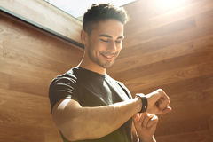 Young man exercise in the gym healthy lifestyle. Young male exercise in the gym checking time Royalty Free Stock Photo