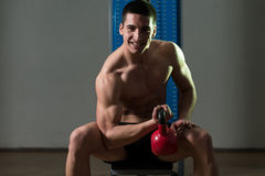 Young Man Exercise With Kettle Bell Biceps. Teenage Boy Exercise With Kettle Bell Biceps Stock Image