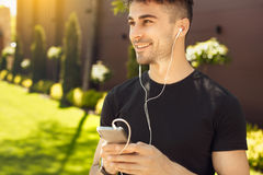 Young man exercise in the park healthy lifestyle. Young male exercise in the park listening music Stock Photography