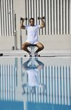 Young man exercise at poolside. Young healthy athlete man exercise at poolside Royalty Free Stock Photography