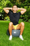 Young man exercises with fitness ball Royalty Free Stock Photography