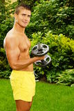 Young man exercisess with dumbells Royalty Free Stock Images