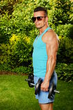 Young man exercisess with dumbells Stock Photo