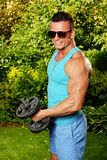 Young man exercisess with dumbells Stock Image