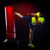 Young man exercising bag boxing in studio Stock Photography