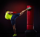 Young man exercising bag boxing in studio Stock Images