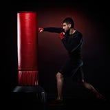 Young man exercising bag boxing in studio Stock Photos
