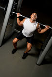 Young man exercising with barbell Squats Royalty Free Stock Images