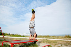 Young man exercising on bench outdoors Stock Photo