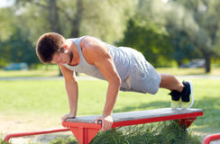 Young man exercising on bench at summer park Royalty Free Stock Images