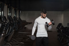 Young Man Exercising Biceps With Dumbbells Stock Photo