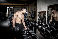 Young man exercising in dark and old gym Stock Photo
