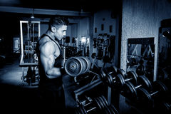 Young man exercising in dark and old gym Stock Photography